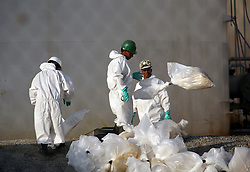20 September 2012. Braithwaite, Plaquemines Parish, Louisiana,  USA. .Private contractors tasked with cleaning up escaped toxins at the Stolthaven chemical plant which was inundated with flood waters from hurricane Isaac. The plant has been accused of failing to prepare for the storm and is suspected of leaking hundreds of thousands of gallons of toxic chemicals into the surrounding area..Photo; Charlie Varley.