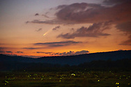 The comet NEOWISE streams across the fiery sky of the dying sun as it sets below the valley painted with the light of fireflies ushering in the veil of stars above.