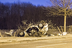 © Licensed to London News Pictures . 02/12/2012 . Bury , UK . Scene of a fatal road traffic accident on Bury Road , Radcliffe . Police report the car , a silver VW Polo , overturned and collided with a tree after it was observed driving at excess speed along Bury Road . A police car with its emergency equipment activated was in pursuit at the time . The driver and a passenger died at the scene . The road is closed . Photo credit : Joel Goodman/LNP