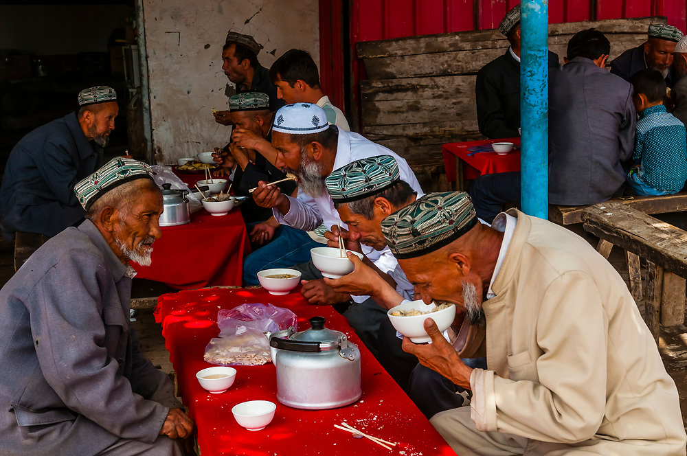 Uyghur men eating lunch at the Sunday Livestock market just outside Kashgar (China's westernmost city), Xinjiang Province, China. Kashgar is along the Silk Road, near Tajikistan and Pakistan. Uyghur people are a Central Asian people of Muslim Turkic origin.