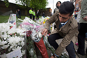 London, UK. Saturday 25th May 2013. Shoaib Zefar (25) from Pakistan, with his parents at the memorial to Drummer Lee Rigby in Woolwich, London, UK. He says that what happened here is not Islam, but that all Islam was peaceful and how important it was fro them to come to pay their respects. Flowers from every section of the local community along with messages of condolence and support. On the afternoon of 22 May 2013, Lee Rigby, a British Army soldier and a Drummer of the Royal Regiment of Fusiliers, was killed by two attackers near the Royal Artillery Barracks in Woolwich, south-east London.
