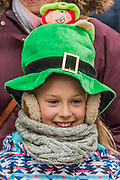 People in many types of green hats are well wrapped up against the cold as they watch the parade go by -  the London St Patrick's Day parade from Piccadilly to Trafalgar Square.