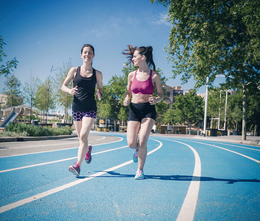 Two women running in the city on a running track