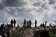 Palestinians watch from atop the rubble of a home belonging to the Samouni family as an Israeli F-15 circles overhead. A total of 29 members of the Samouni family were killed during Operation Cast Lead.
