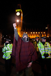 "© licensed to London News Pictures. London, UK 17/01/12. A protester stands in front of police outside the ""Democracy Village"" protest camp at Parliament Square in London which was cleared by police last night (16/01/12). Photo credit: Tolga Akmen/LNP"
