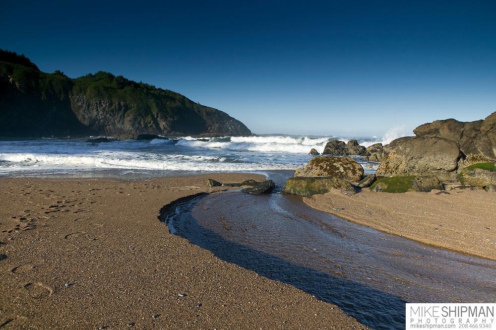 A stream runs into the ocean at Fogarty Beach, Oregon, Lincoln County, USA