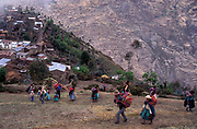 Revellers ascend from the remote village of Curva towards the cemetery during the Day of The Dead festivities, where they share their drinks and feast with the spirits of the dead. Curva is home to the Kallawaya Indians who practice shamanistic medicine.Bolivia.