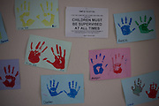 A notice and childrens handprint paintings on the wall of the visitors centre. HMP Styal, Wilmslow, Cheshire