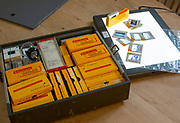Yellow films storage boxes holding Kodachrome vintage transparency slides dating from 1960s with Lightbox for editing images
