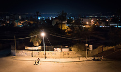 6 October 2018, Jericho, Occupied Palestinian Territories: A mother and her child walk down the streets of Jericho at night.