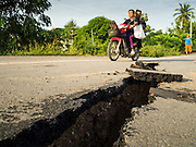 14 JULY 2015 - THAILAND:  A family drives on a damaged road in Pathum Thani province. The road bed collapsed because of subsidence. The drought that has crippled agriculture in central Thailand is now impacting residential areas near Bangkok. The Thai government is reporting that more than 250,000 homes in the provinces surrounding Bangkok have had their domestic water cut because the canals that supply water to local treatment plants were too low to feed the plants. Local government agencies and the Thai army are trucking water to impacted communities and homes. Roads in the area have started collapsing because of subsidence caused by the retreating waters. Central Thailand is contending with drought. By one estimate, about 80 percent of Thailand's agricultural land is in drought like conditions and farmers have been told to stop planting new acreage of rice, the area's principal cash crop.      PHOTO BY JACK KURTZ