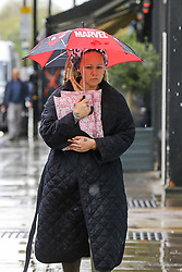 © Licensed to London News Pictures. 10/05/2021. London, UK. A woman shelters from rain beneath a children's umbrella in north London. More rain is forecast for the South East of England this week. Photo credit: Dinendra Haria/LNP