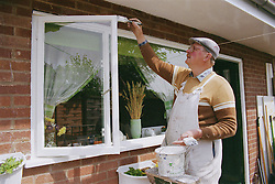 Painter and decorator at work painting window frame,