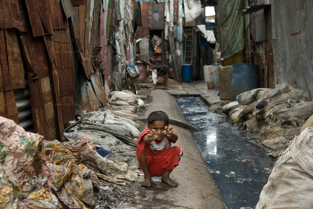 A boy plays next to the open gutter next to his home in the plastic recycling area. Dharavi, August 2007