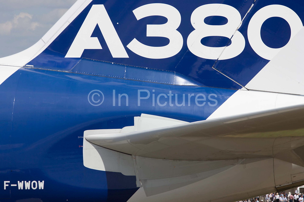 Airbus A380 jet airliner tail (in generic Airbus colours) at the Farnborough Air Show, England. The huge tail of the largest airliner in the world, scales the perspective of the corporate building alongside. At the 2014 show, Airbus announced new business worth more than $75m for 496 aircraft, a new record for the company. The Airbus A380 is a double-deck, wide-body, four-engine jet airliner manufactured by Airbus. It is the world's largest passenger airliner, and many airports have upgraded facilities to accommodate its size.