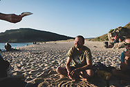 Mantas, from Lithuania, relaxes with other pilgrims who have finished their caminos at Playa Mar de Fora in Finisterre, Spain. (July 19, 2018)<br />