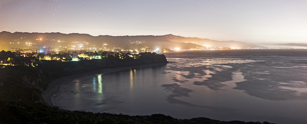 The lights of cars outline highway 1 along the Malibu shoreline, as seen from the top of point dude.