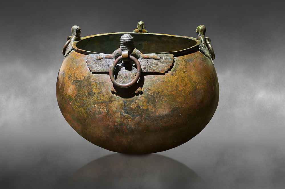 Phrygian bronze couldron with decorated winged figure handles . From Gordion. Phrygian Collection, 8th century BC - Museum of Anatolian Civilisations Ankara. Turkey. Against a grey background .<br /> <br /> If you prefer you can also buy from our ALAMY PHOTO LIBRARY  Collection visit : https://www.alamy.com/portfolio/paul-williams-funkystock/phrygian-antiquities.html  - Type into the LOWER SEARCH WITHIN GALLERY box to refine search by adding background colour, place, museum etc<br /> <br /> Visit our CLASSICAL WORLD PHOTO COLLECTIONS for more photos to download or buy as wall art prints https://funkystock.photoshelter.com/gallery-collection/Classical-Era-Historic-Sites-Archaeological-Sites-Pictures-Images/C0000g4bSGiDL9rw