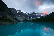 Several mountains in the Canadian Rockies tower over Moraine Lake, located in Banff National Park. This area is known as the Valley of the Ten Peaks, named for the ten tall mountains at the lake's edge. Moraine Lake has a unique aqua color that results from the silt deposited by glaciers.