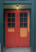 A colorful red door with green and blue trim a single overhead lightbulb, and multiple panes of glass.