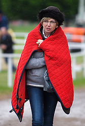 © Licensed to London News Pictures. 12/05/2018. Windsor, UK. A horse owner wrapped up during cold and damp conditions in the afternoon at day 4 of the 75th Royal Windsor Horse Show . The five day event takes place in the grounds of Windsor Castle. Photo credit: Ben Cawthra/LNP