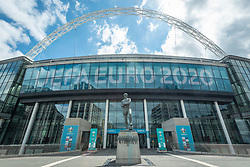 © Licensed to London News Pictures. 10/06/2021. LONDON, UK.  The Bobby Moore statue and signage around Wembley Stadium for the upcoming 2020 UEFA European Football Championship, commonly known as Euro 2020.  The tournament was postponed from 2020 due to the COVID-19 pandemic in Europe and rescheduled for 11 June to 11 July 2021 with matches to be played in 11 cities in 11 UEFA countries.  Wembley Stadium will host certain group matches including England v Croatia on 13 June, as well as the semi-finals and final itself.  Photo credit: Stephen Chung/LNP