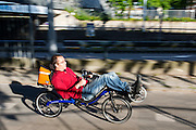 In Utrecht rijdt een man op een ligfiets over de Amsterdamsestraatweg.<br /> <br /> In Utrecht a man is riding a recumbent bicycle at the Amsterdamsestraatweg.