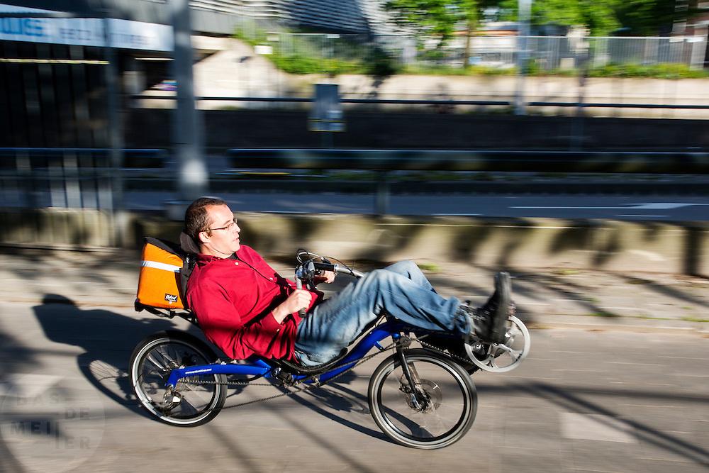 In Utrecht rijdt een man op een ligfiets over de Amsterdamsestraatweg.<br /> <br /> In Utrecht a man is riding a recumbent bicycle at the Amsterdamsestraatweg.