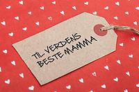 Gavelapp med påskrift «Til verdens beste mamma», på rødt gavepapir med hjerter. Illustrasjonsbilde til tema jul, gebursdag eller morsdag.