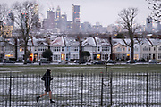 With bare legs, a runner wears shorts and passes snow-covered roofs of south London Edwardian homes and residential high-rise towers under construction, on 8th February 2021, in London, England.