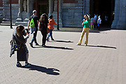 Asian tourist photographing friend in front of the Rijksmuseum amsterdam