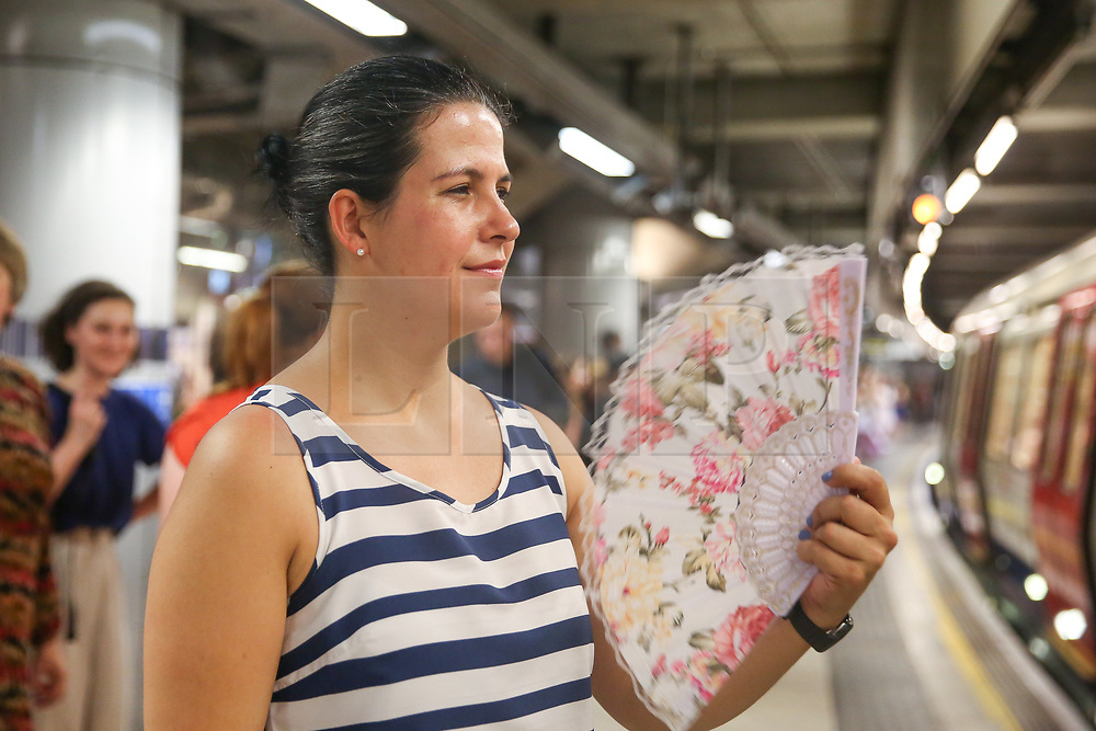 © Licensed to London News Pictures. 25/07/2019. London, UK. Janaina uses a hand held fan to cool down at Westminster underground platform while waiting for a train. According to the Met Office, today will be the hottest day of the year and temperatures are expected to break records. <br /> <br /> ***Permission Granted***<br /> <br /> Photo credit: Dinendra Haria/LNP