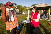 18 SEPTEMBER 2020 - FT. DODGE, IOWA: THERESA GREENFIELD (right, red vest) talks with an Iowa voter with an elbow bump in H.C. Meriwether Park in Ft. Dodge. Greenfield, the Democratic candidate for US Senate, visited a National Black Voter Day voter registration event in Ft. Dodge, about 100 miles north of Des Moines. Greenfield is running against incumbent US Senator Joni Ernst, a Republican.       PHOTO BY JACK KURTZ