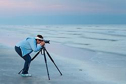 Photographer on beach at sunset on Gulf of Mexico, Galveston Island State Park, Galveston, Texas, USA