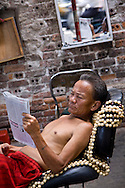 Barber reading a newspaper in a street of Hanoi, Vietnam, Asia
