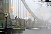 © Licensed to London News Pictures. 21/01/2014. Hammersmith, UK People cross Hammersmith Bridge in heavy fog in West London today 21st January 2014. Photo credit : Stephen Simpson/LNP