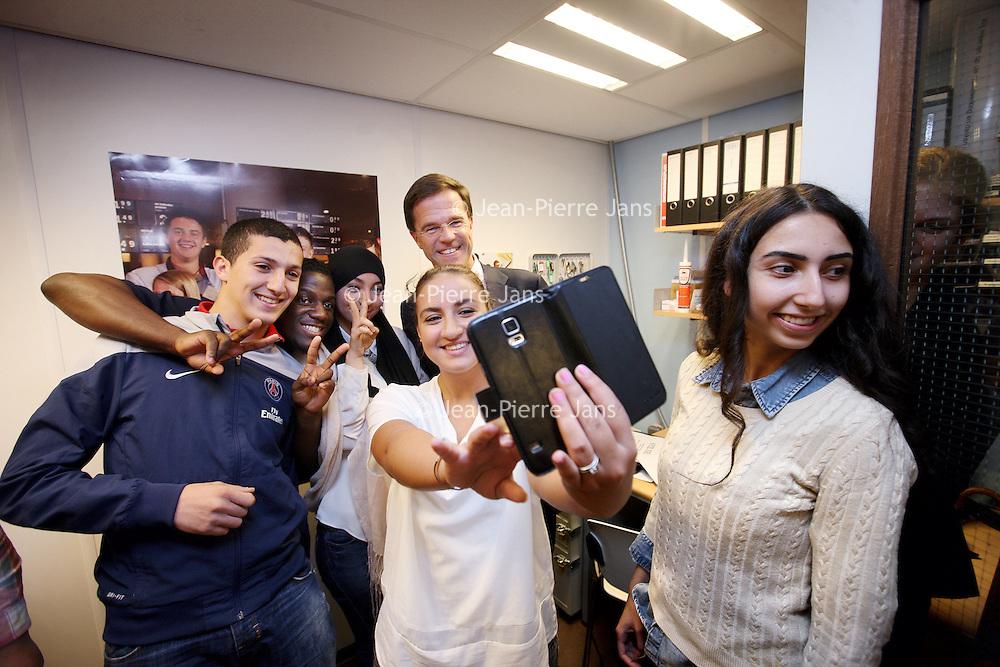 Nederland, Amsterdam , 30-10-2014.<br /> Bedrijfsbezoek van minister-president Mark Rutte op uitnodiging van Ahold/Albert Heijn aan Albert Heijn filiaal in de Molukkenstraat in Amsterdam Oost.<br /> Op de foto: Mark rutte in gesprek met scholieren en medewerkers van AH in de zg studieruimte, een plek waar de jongeren hun huiswerk kunnen doen als er thuis geen plek voor is en daarna op de selfie.<br /> <br /> <br /> Foto:Jean-Pierre Jans/ANPinOpdracht