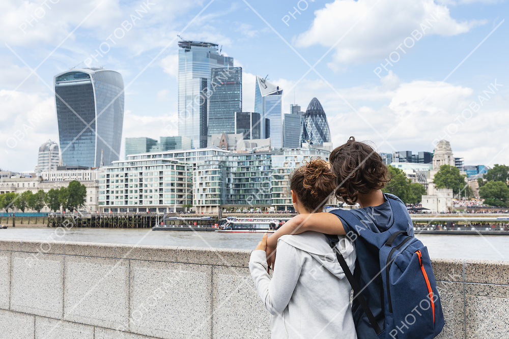 Two guys hold each other while watching the London skyline on a summer day