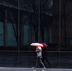 London, January 02 2018. A woman with a pink umbrella is reflected in a building as rain descends on the capital. © SWNS