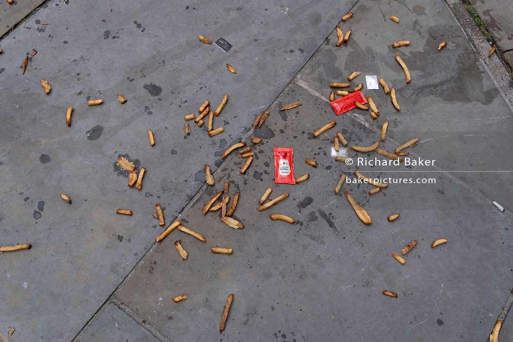 Along with sachets of salt and tomato ketchup, the remains of a portion of chips (aka French Fries) lie scattered on the pavement on London's Southbank, on 10th June 2021, in London, England.