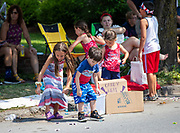 Children pick up candy thrown to them during the Independence Day parade in Millville, Pennsylvania on July 5, 2021.