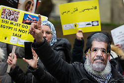 London, UK. 25 January, 2020. A man wears a mask bearing the image of the late Egyptian President Mohamed Morsi at a protest outside Parliament against the Egyptian government of President Abdel Fattah el-Sisi by supporters of the Egyptian Revolutionary Council and UK anti-Coup organisations.
