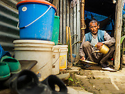 01 MARCH 2017 - KHOKANA, NEPAL: A man washes his dishes in front of the shelter he lives in at an informal IDP camp in Khokana. His home was destroyed was destroyed in the 2015 earthquake. Recovery seems to have barely begun nearly two years after the earthquake of 25 April 2015 that devastated Nepal. In some villages in the Kathmandu valley workers are working by hand to remove ruble and dig out destroyed buildings. About 9,000 people were killed and another 22,000 injured by the earthquake. The epicenter of the earthquake was east of the Gorka district.     PHOTO BY JACK KURTZ