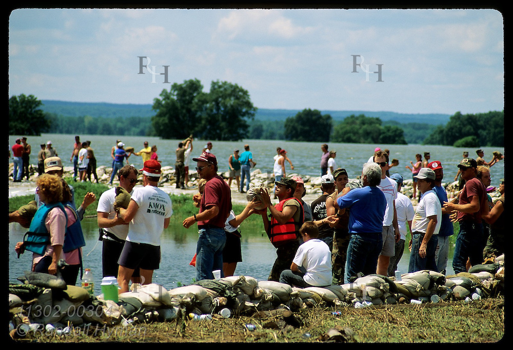Local folks toss sandbags along levee as Mississippi laps at top on 8/4/93; Prairie du Rocher. Illinois
