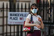 People wearing personal protective masks walk near Oxford Street in London on Thursday, May 28, 2020. The government in Britain eased restrictions across England as a slow loosening of the coronavirus lockdown gets underway, with people now encouraged to return to work if unable to do so from home and unlimited outdoor exercise now allowed. As the row over Prime Minister Boris Johnson's top aide Dominic Cummings' Durham trip, continues, the prime minister's populist appeal has been hammered by the news and members of the public that, as the coronavirus outbreak raged, chief adviser Cummings drove 250 miles (400 kilometres) to his parents' house while he was falling ill with suspected COVID-19 allegedly flouting lockdown rules that the government had imposed on the rest of the country. (Photo/ Vudi Xhymshiti)