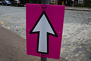 White arrow on a pink board showing the direction to an event in London, England, United Kingdom.
