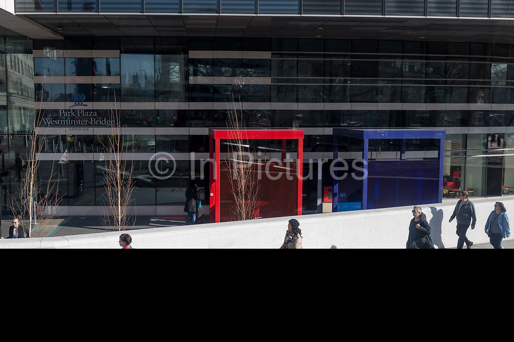 Pedestrians walk past two outdoor smokers' cubicles located at the Park Plaza Hotel at the southern end of Westminster Bridge, on 27th February, in London, England.