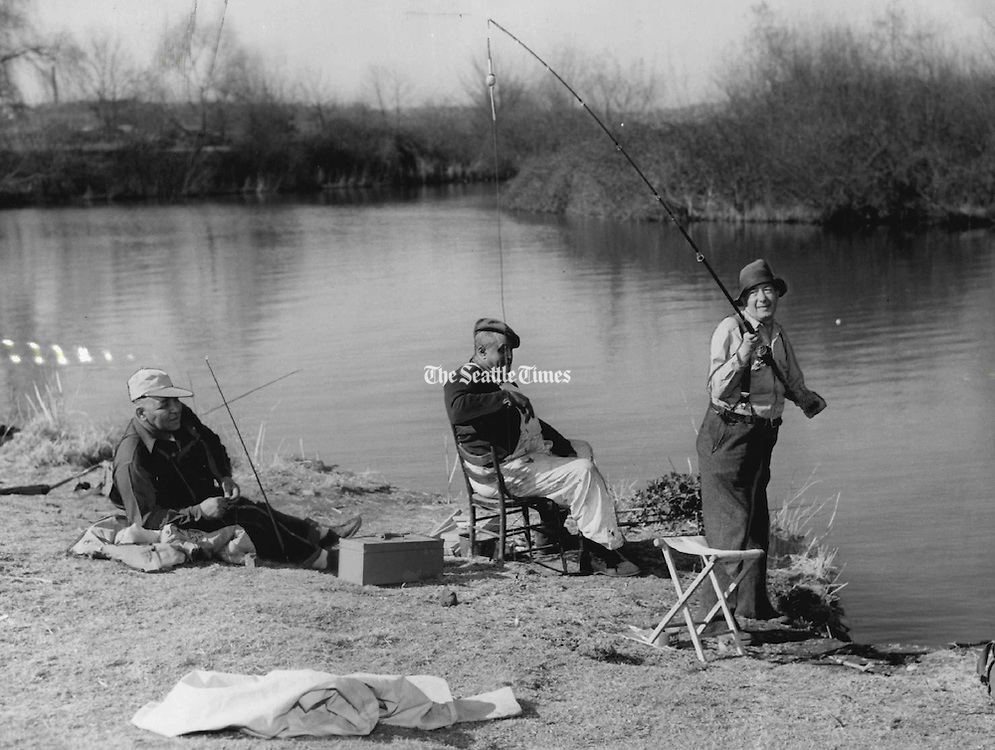 """Spring Refuge: Superior Judge William G. Long, talking refuge from court affairs, prepared to fling his bait across a placid lake inlet bordering the University of Washington Arboretum yesterday. The jurist said he, like thousands of Seattleites, was lured outdoors by the warm spring weather. Watching were, from left, two other cat fishing fans, Carl Smith and Walter Derrick, who remarked: """"The judge has enough bait to catch a bear.""""<br /> (Vic Condiotty / The Seattle Times, 1955)"""