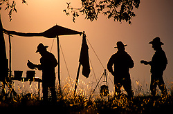 silhouette of three men standing at an old western campsite