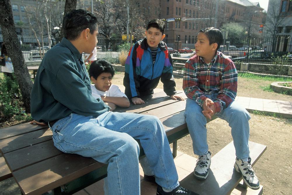 Four Hispanic boys of different ages talk outside Catholic San Fernando Cathedral in San Antonio, Texas.  Model Release. ©Bob Daemmrich